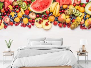 Variety of colorful organic fruits and berries on white table background, top view, border. Healthy food and vegetarian eating concept