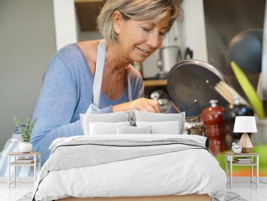 Senior woman in home kitchen cooking for dinner