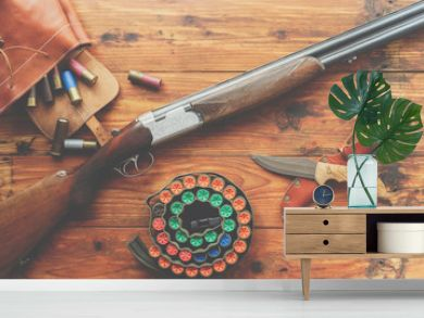 Hunting equipment. Shotgun, hunting cartridges and hunting knife on wooden table.