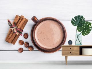 Hot cocoa with milk in brown clay cup, hazelnut and cinnamon sticks on table of white wooden planks, top view
