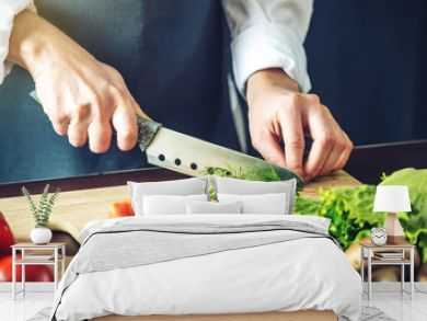 The chef in black apron cuts vegetables. Concept of eco-friendly products for cooking