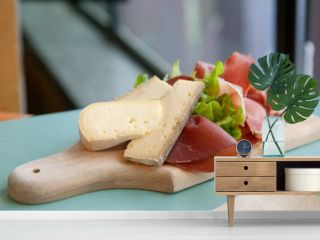 Cutting board with cheese and hum on table in cafe