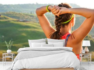 sportswoman against scenery of Tuscany looking into distance