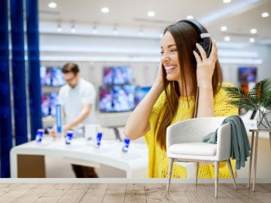 Close up of adorable attractive happy girl testing headphones in a tech store.
