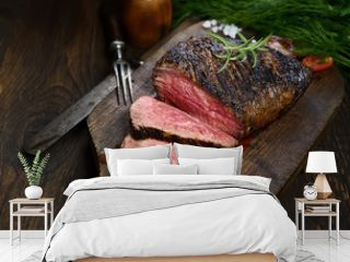 grilled steak with rosemary on a cutting board on a black background