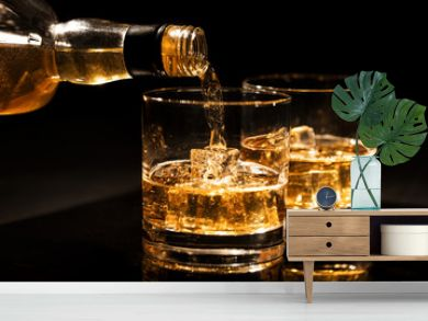 pouring whiskey into a glass with ice cubes on black background