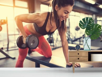 Sportswoman in gym exercise muscles