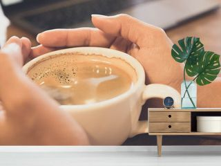 Closeup of hands are  holding a white cup of black coffee on wood table in coffee cafe