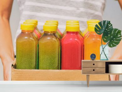 Woman holding delivery box of freshly cold pressed fruit and vegetable juice bottles. Trendy young person carrying organic raw juices. Juicing is a food trend for diet cleanse detox. Banner panorama.