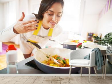 Young charming pretty woman is smiling while smelling the aroma of her fresh healthy breakfast being cooked.