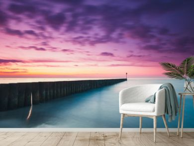 Sunset on the beach with a wooden breakwater, purple tone