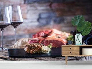 Two cups with red wine roasted and raw beef steak on slate board