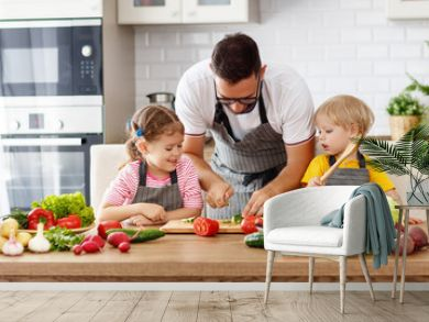 father with children preparing vegetable salad