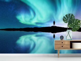 Northern lights and silhouette of standing man in the hill in Norway. Aurora borealis and man. Stars and green polar lights. Night landscape with aurora, lake, sky reflection in water. Travel. Concept