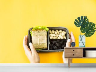 Female hands hold lunchbox with food - sandwich, nuts and berries on a yellow background. Top view, flat lay,