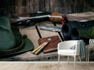 Professional hunters equipment for hunting. Detail on the ammunition.  Wooden black background with rifle, hat, and other equipment for hunting.