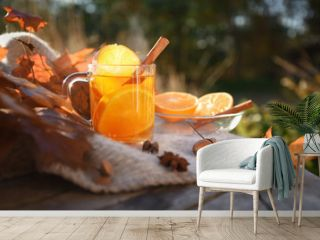 hot tea with orange slices and cinnamon on a wooden garden table with a blanket and autumn leaves, copy space