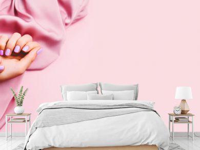 Beautiful woman manicure on creative pink background with silk fabric. Minimalist trend.