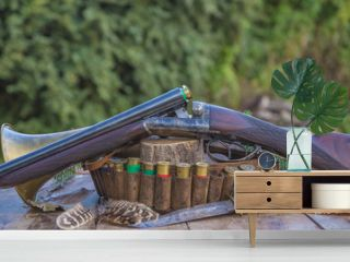 Beautiful vintage hunting gun, cartridges, knife, horn, feather on wooden table outdoors