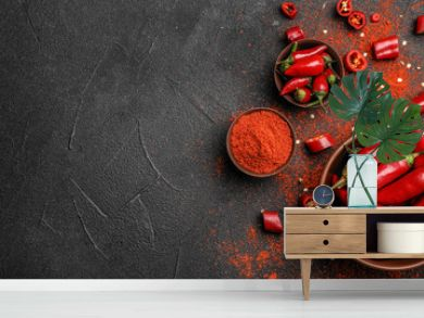 Flat lay composition with powdered and raw chili peppers on dark background. Space for text