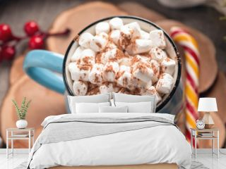 Mug of hot chocolate with marshmallow on top and Lollipop stick on wooden background. Cozy warm winter composition