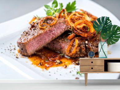 Klassischer Zwiebelrostbraten serviert mit Röstzwiebel und Kräuter als closeup auf einem Modern Design Teller