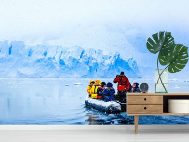 Snowfall over the boat with frozen tourists driving towards the huge blue glacier wall in the background, near Almirante Brown, Antarctic peninsula