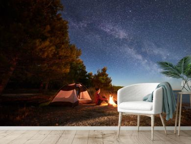 Night camping on shore. Man and woman hikers having a rest in front of tent at campfire under evening sky full of stars and Milky way on blue water and forest background. Outdoor lifestyle concept