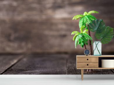 Small toy of palm tree on wooden background