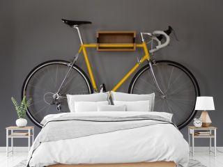 Ein geles Fahrrad an einer Halterung an einer grauen Wand in der Wohnung.
