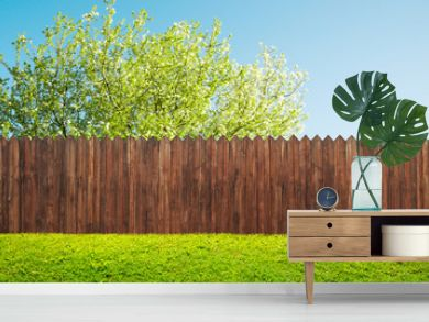 a wooden garden fence at backyard and bloom tree in spring