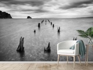 Long old wooden pier (bridge) extents from beach to sea. Deep cloudy sky after the big storm. Expectation to success dreams,Travel and summer Vacation. Beautiful landscape background concept