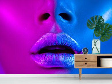 Beautiful sexy girl, trendy glowing makeup, metallic silver lips. High fashion model woman in colorful bright neon lights posing in studio.