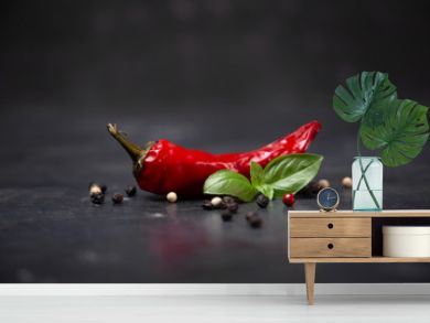 chili pepper with basil and peppercorns on a rustic surface