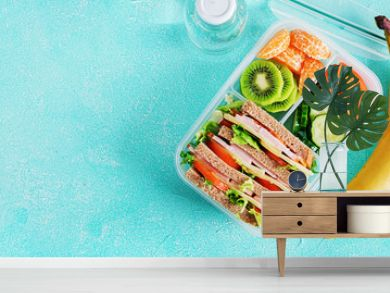 School lunch box with sandwich, vegetables, water, and fruits on table. Healthy eating habits concept. Flat lay. Top view