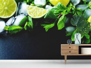 Mojito coctail ingredients with fresh mint leaves and lime slices on a black background