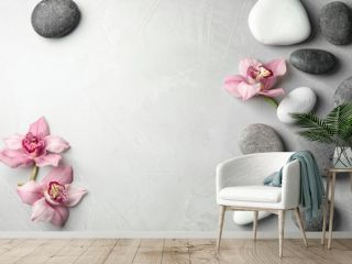 Zen stones and exotic flowers on grey background, top view with space for text
