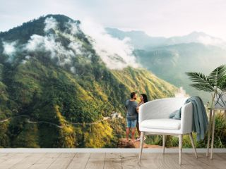The couple greets the sunrise in the mountains. Man and woman in the mountains. Man and woman hugging. The couple travels around Asia. Travel to Sri Lanka. Serpentine in the mountains. Honeymoon