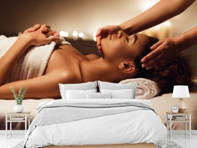 Face massage. African-american woman getting spa treatment