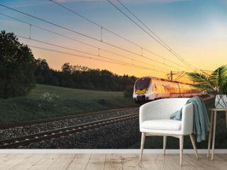 Modern German train traveling at sunset