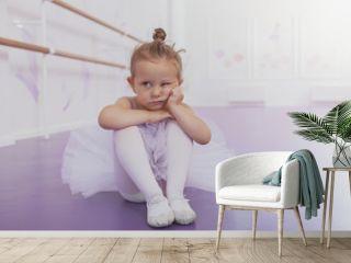 Adorable little girl ballerina looking grumpy, sitting alone on the floor at ballet school, copy space. Cute little ballerina looking bored and annoyed at ballet dancing class