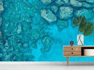 An aerial view of the beautiful Mediterranean Sea, with a wooden pier and a rocky shore, where you can see the textured underwater corals and the clean turquoise water of Protaras, Cyprus