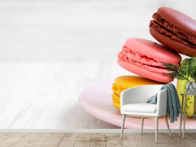 Sweet and colorful macarons on a pink plate over white wooden background, side view. Copy space.