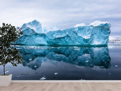 Impressive iceberg with blue ice and beautiful reflection on water in Antarctica, scenic landscape in Antarctic Peninsula