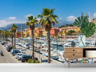 View of palm tree and harbor with boats in Menton on French Riviera. Provence-Alpes-Cote d'Azur, France.