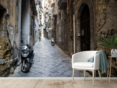 Scenic view of typical narrow alleyway lined with scooters and laundry lines in the Medieval Centro Storico of Naples, Italy