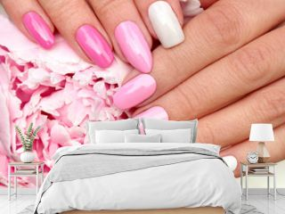 Light pink, pastel manicure on various shapes of nails with peony closeup.