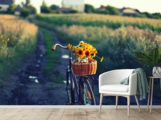 a bicycle with a bouquet of yellow flowers in a basket against nature background