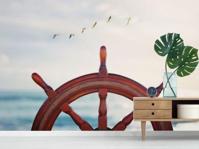 vintage nautical detail of a steering wheel of a ship in front of the sea at sunset