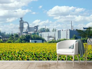 Industrial buildings near a sunflower field on a sunny day
